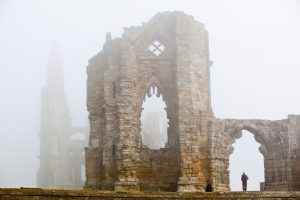 The ruins of Whitby abbey on a misty day with man in an arch