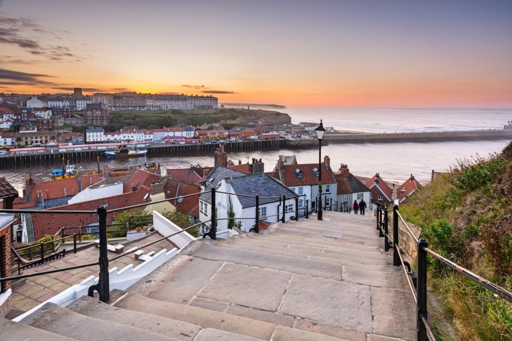 Photo looking down steps over the red roofs of the cottages to Whitby harbour with sunset in background over the sea