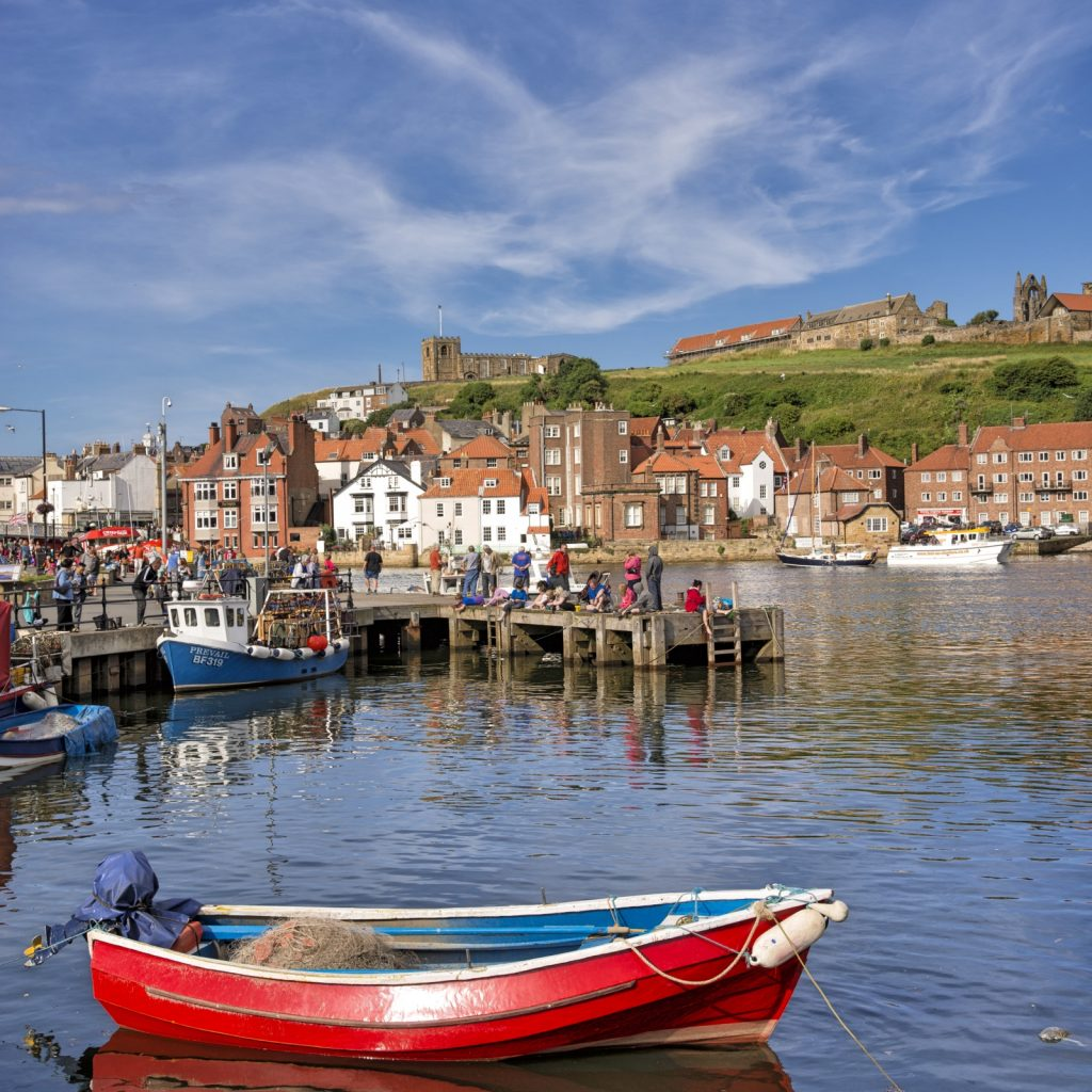 Looking from the water over a red fishing boat to the jetty with people on and beyond to the houses of Whitby harbour