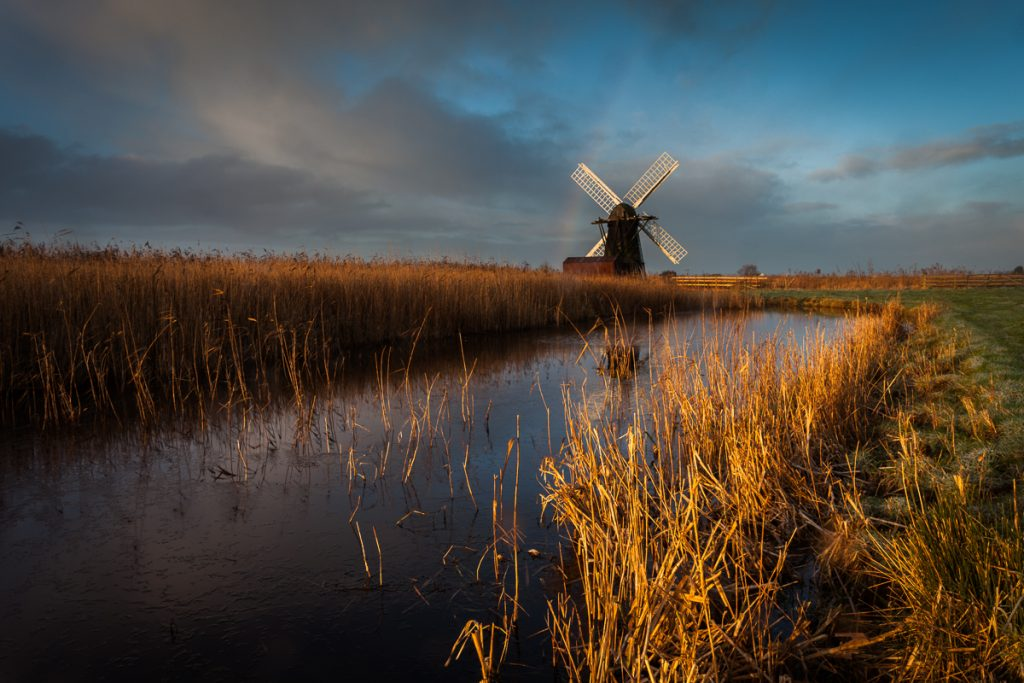 View down the river with reeds each side to a black and white wooden windmill at the end, cloudy sky